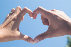 Beautiful Love shape hands - heart on blue sky Stock Photography