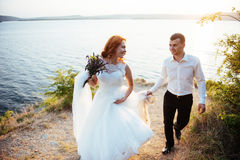 Beautiful lovely blonde bride and groom classy on the rocks, ami Royalty Free Stock Photo