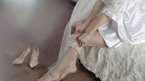Beautiful and lovely bride in night gown. Dress up the garter on the leg. Wedding morning. Pretty and well-groomed woman. Slow mot stock video footage