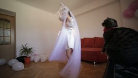 Beautiful and lovely bride in night gown holds hanger with a wedding dress and dance with this dress. Cat sits near woman. Wedding morning. Pretty and well stock video