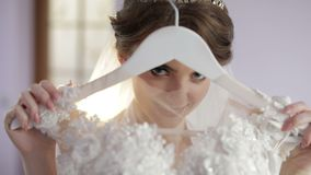 Beautiful and lovely bride in night gown holds hanger with a wedding dress. Wedding morning. Pretty and well-groomed woman. Slow motion stock video footage