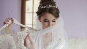 Beautiful and lovely bride in night gown holds hanger with a wedding dress. Wedding morning. Pretty and well-groomed woman. Slow motion stock video