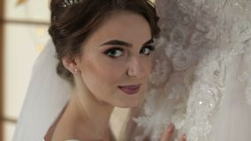 Beautiful and lovely bride in night gown stands near wedding dress and looks at camera. Close-up shot. Wedding morning. Pretty and well-groomed woman. Slow stock video footage
