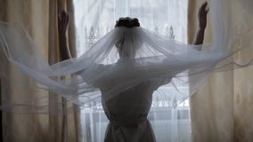 Beautiful and lovely bride in night gown and veil. Wedding morning. Slow motion. Beautiful and lovely bride in night gown. Throws up her veil near window stock video footage
