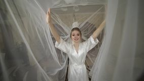 Beautiful and lovely bride in night gown under huge veil. Wedding morning. Beautiful and lovely bride in night gown under huge veil. Pretty and well-groomed stock footage