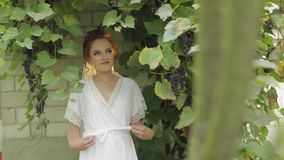 Beautiful and lovely bride in night gown and veil in the garden. Wedding morning. Beautiful and lovely bride in night gown and veil in the grape garden. Pretty stock footage