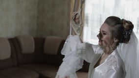 Beautiful and lovely bride in night gown and veil holds wedding dress. Pretty and well-groomed woman. Wedding morning. Slow motion stock video