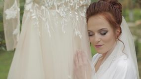 Beautiful and lovely bride in night gown and veil. Wedding dress. Slow motion. Beautiful and lovely bride in night gown and veil near wedding dress which hangs stock video
