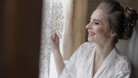 Beautiful and lovely bride in night gown and veil. Wedding morning. Slow motion. Beautiful and lovely bride in night gown and veil near window. Pretty and well stock video