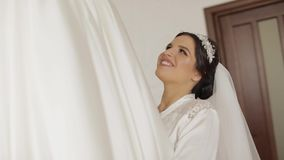 Beautiful and lovely bride in night gown and veil running to wedding dress. Pretty and well-groomed woman. Wedding morning. Slow motion stock footage