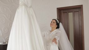 Beautiful and lovely bride in night gown and veil running to wedding dress. Pretty and well-groomed woman. Wedding morning. Slow motion stock video footage