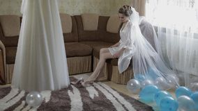 Beautiful and lovely bride in night gown and veil. Wedding dress. Slow motion. Beautiful and lovely bride in night gown and veil sit on the sofa with balloons stock footage