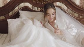 Beautiful and lovely bride in night gown and veil sitting and drinking champagne. Beautiful and lovely bride in night gown sitting on bed and drinking champagne stock footage