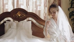 Beautiful and lovely bride in night gown and veil sitting and drinking champagne. Beautiful and lovely bride in night gown sitting on bed and drinking champagne stock video