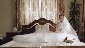 Beautiful and lovely bride in night gown and veil sitting and drinking champagne. Beautiful and lovely bride in night gown sitting on bed and drinking champagne stock video footage