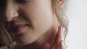 Beautiful and lovely bride in night gown and veil touches her earrings. Pretty and well-groomed woman in nightdress. Wedding morning. Slow motion stock video footage