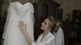 Beautiful and lovely bride in night gown and veil. Wedding dress. Slow motion. Beautiful and lovely bride in night gown and veil near wedding dress. Pretty and stock video