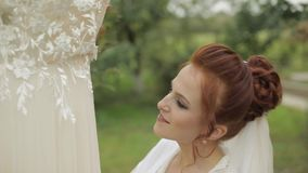 Beautiful and lovely bride in night gown and veil. Wedding dress. Slow motion. Beautiful and lovely bride in night gown and veil near wedding dress which hangs stock footage