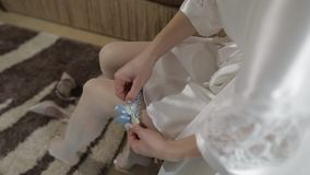 Beautiful and lovely bride in night gown wears wedding garter on her leg. Pretty and well-groomed woman. Wedding morning. Close-up shot. Slow motion stock footage