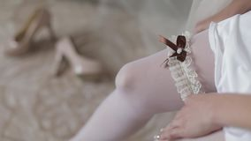 Beautiful and lovely bride in night gown wears wedding garter on her leg. Pretty and well-groomed woman. Wedding morning. Slow motion stock footage
