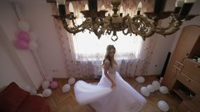 Beautiful and lovely bride in wedding dress dancing near window. Wedding morning. Pretty and well-groomed woman. Slow motion stock footage