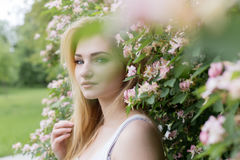 Beautiful lovely girl with long blonde hair enjoying nature near blooming rosebush in a white t-shirt with full lips bright summer Stock Photography
