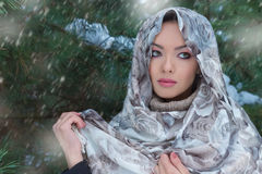 Beautiful lovely girl standing under snow in a scarf and warm sweater in the winter forest near the trees royalty free stock images