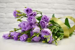 Beautiful lovely lilac eustoma with a satin ribbon on white table stock photos