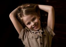 Beautiful lovely little blonde girl with different emotions on a dark background royalty free stock image