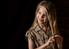 Beautiful lovely little blonde girl with different emotions on a dark background stock photography