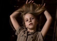 Beautiful lovely little blonde girl with different emotions on a dark background.  stock photo