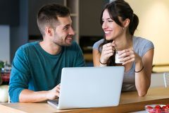 Beautiful lovely young couple using their laptop and having breakfast in the kitchen at home. royalty free stock photos