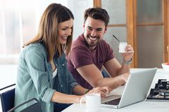 Beautiful lovely young couple using their laptop and having breakfast in the kitchen at home royalty free stock images