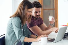 Beautiful lovely young couple using their laptop and having breakfast in the kitchen at home royalty free stock photos