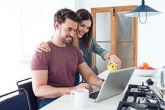 Beautiful lovely young couple using their laptop and having breakfast in the kitchen at home royalty free stock photography