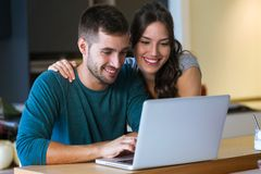 Beautiful lovely young couple using their laptop in the kitchen at home. royalty free stock photos