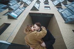 Beautiful lovers kissing near modern apartment building. Winter street, snowy day. New settlers, new life royalty free stock photo
