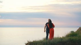 Beautiful loving couple on the edge of the cliff looking at the sunset stock footage