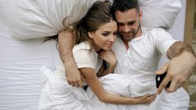Young beautiful and loving couple having online vidoe call with smartphone camera while lying in bed at the morning. Beautiful and loving couple having online stock photo