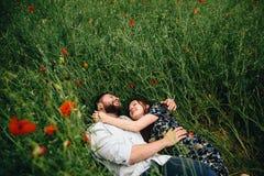 Beautiful loving couple lying on poppies field background stock photo