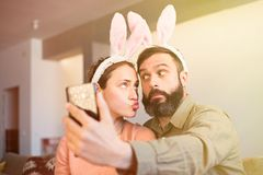 Beautiful loving couple making selfie on smartphone with pink rabbit ears on head. Happy family preparing for Easter. Beautiful loving couple making selfie on stock photography