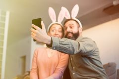 Beautiful loving couple making selfie on smartphone with pink rabbit ears on head. Happy family preparing for Easter. Beautiful loving couple making selfie on royalty free stock photos