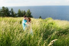beautiful loving couple resting in summer field on big grass, caressing each other and kissing. Couple in the grass royalty free stock photos