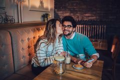 Beautiful loving couple sitting in a cafe drinking coffee. And conversating. Love and romance concept royalty free stock image