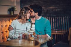 Beautiful loving couple sitting in a cafe drinking coffee. And conversating. Love and romance concept royalty free stock photos