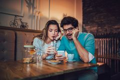 Beautiful loving couple sitting in a cafe drinking coffee. And using phone. Love and romance concept stock image