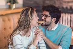 Beautiful loving couple sitting in a cafe sharing cookie. Love and romance concept Stock Images