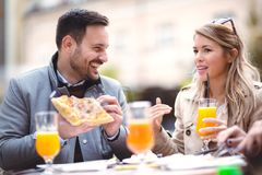 Beautiful loving couple sitting in outdoor cafe and eating pizza Stock Photography