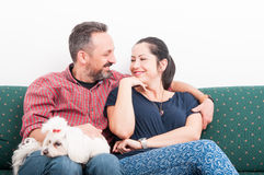 Beautiful loving couple sitting on sofa and embracing royalty free stock images