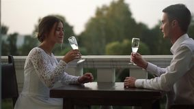 Beautiful loving couple sitting at a table in a restaurant outdoors on their wedding day. Lovers looking at each other, talk, laugh and clink glasses. The stock video